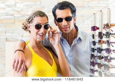 couple at optician or optometrist buying sunglasses