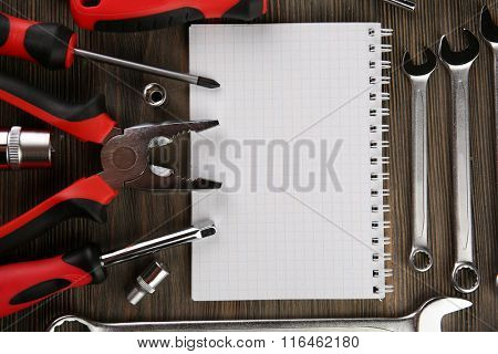 Different kinds of tools with a notebook on wooden background, closeup
