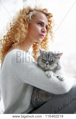 Young woman and cat in the room