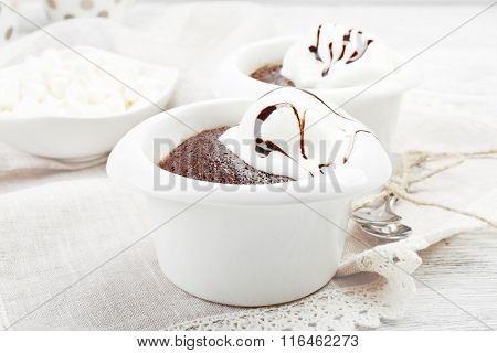 Chocolate lava cake with ice-cream in bowls, on the table