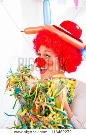 Funny clown on party or carnival with paper streamers in her hand