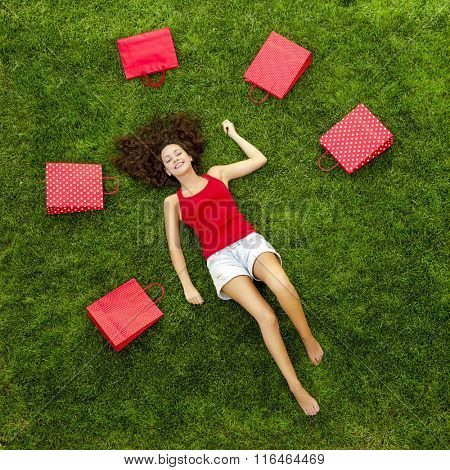 Beautiful and happy young woman lying on the grass surrounded by red gift bags
