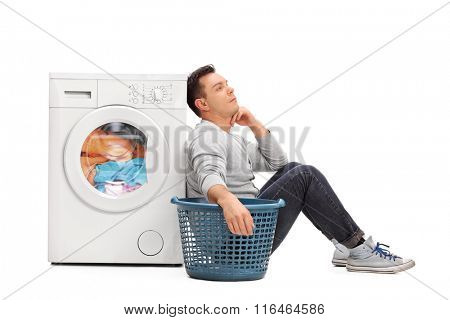 Bored young man sitting by a washing machine and waiting for the laundry isolated on white background
