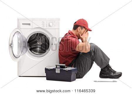Studio shot of a disappointed young repairman sitting by a broken washing machine isolated on white background