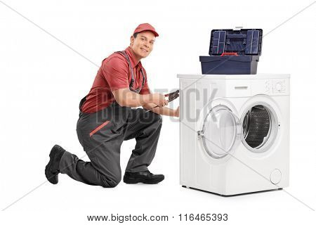 Young repairman fixing a washing machine and looking at the camera isolated on white background