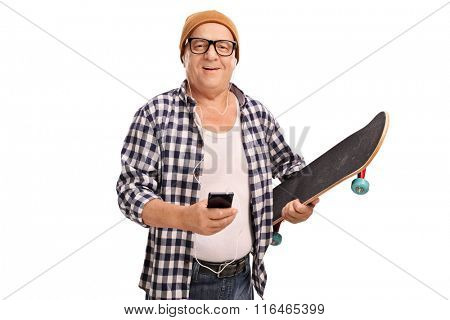 Cool senior skater holding a skateboard and listening music on headphones isolated on white background