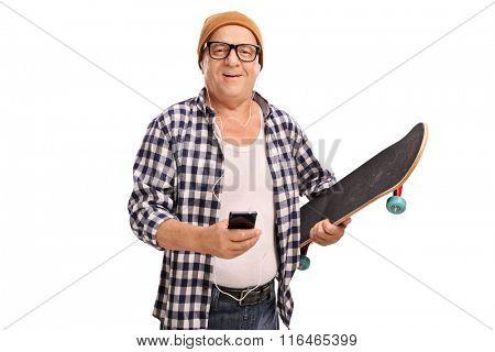 Cool senior skater holding a skateboard and listening music on headphones isolated on white background
