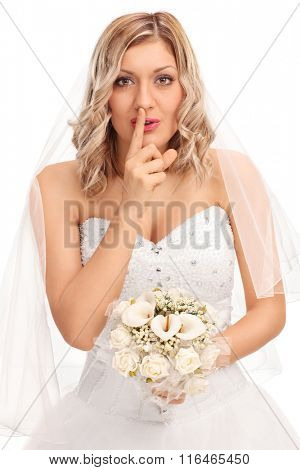 Vertical shot of a young blond bride holding a wedding flower and a finger on her lips isolated on white background