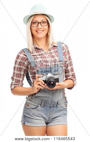 Vertical shot of a blond hipster girl holding a camera and smiling isolated on white background