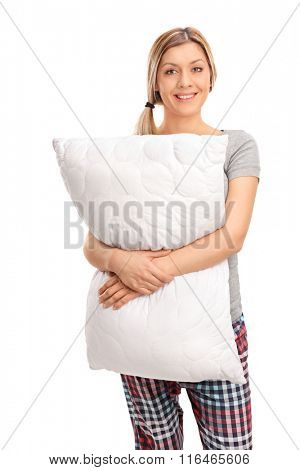 Vertical shot of a cheerful blond woman hugging a pillow and looking at the camera isolated on white background