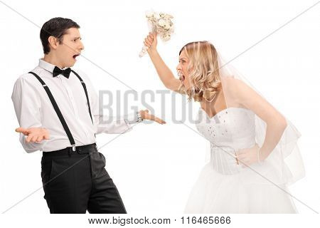 Studio shot of a young bride yelling to the groom and threatening him isolated on white background