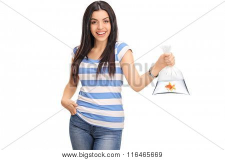 Studio shot of a young woman holding a plastic bag with water and a goldfish in it isolated on white background