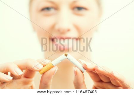 Happy woman breaking cigarette