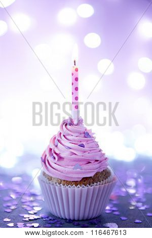 Cupcake with pink cream icing and candle on a glitter background, close up