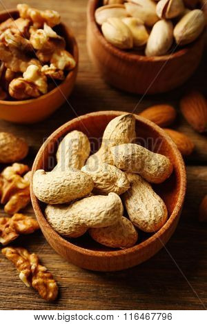 Pistachios, almonds, peanuts and walnut kernels in the wooden bowls on the table, close-up