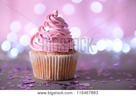 Cupcake with pink cream icing on a glitter background, close up
