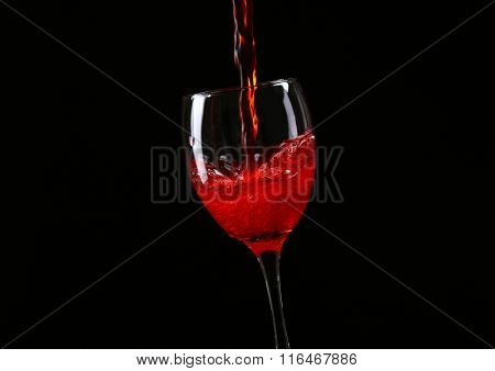 Wine pouring in glass on black background