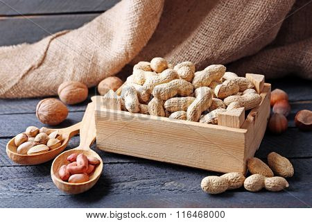 Pistachios in the wooden box and other nuts on the table