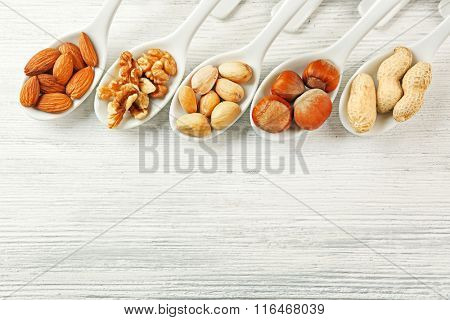 Walnut kernels, almonds, pistachios, hazelnuts and peanuts in the ceramic spoons on the wooden table