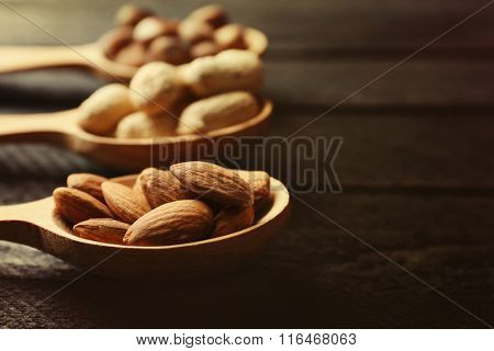 Spoons with almonds, acorns and peanuts, on grey wooden background