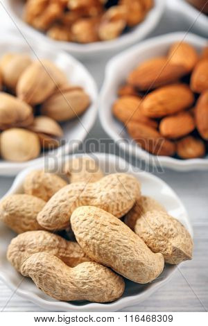 Peanuts, pistachios, almonds and walnut kernels in the bowls, close-up
