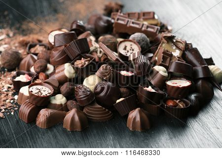 Assortment of tasty chocolate candies on wooden table background