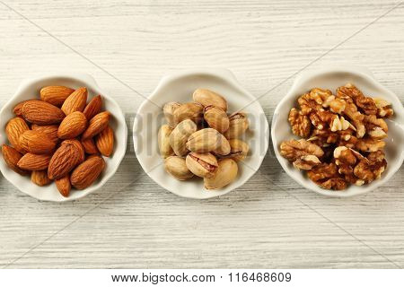 Pistachios, almonds and walnut kernels in the bowls on white wooden table