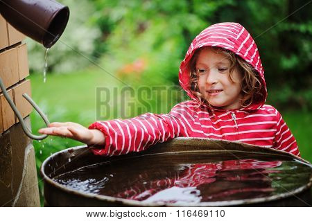 child girl in red raincoat playing with water barrel in rainy summer garden. Water economy and natur