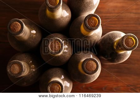 Stacks of dusty wine bottles on wooden background, upside view.