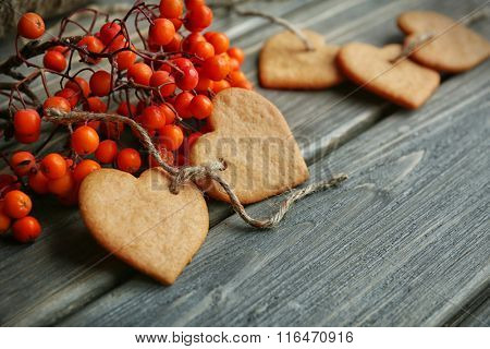 Heart shaped biscuits with ash berries and thread on wooden background