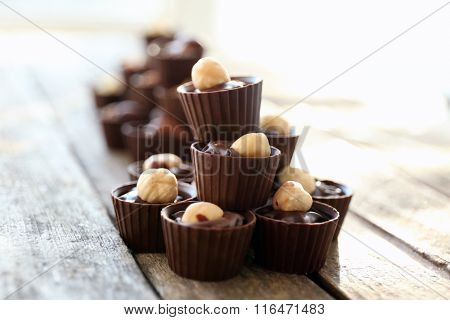 Composition of different chocolate candies on wooden background, close up