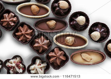 Composition of chocolate candies on white background, close up
