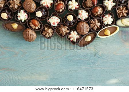 Assorted chocolate candies on wooden background, close up