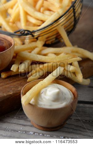 French fried potatoes in metal basket on wooden background