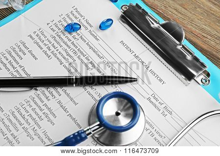 Medical stethoscope, clipboard, pills and pen on the table