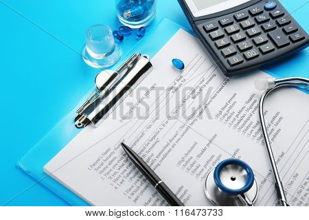 Medical stethoscope, clipboard, pen and calculator, close-up