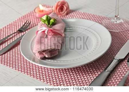 Table setting with dishes, napkin, cutlery and candle on pink background