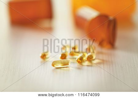 Capsules spilled from orange pill bottle on wooden table, blurred