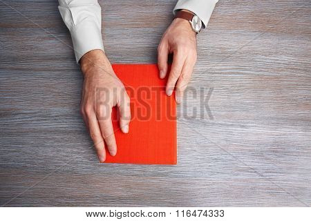 Man hands holding book, on wooden table background