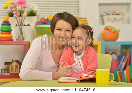 Daughter and mother reading the book