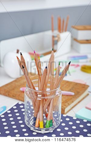 Set of coloured pencils in glass jar on a table