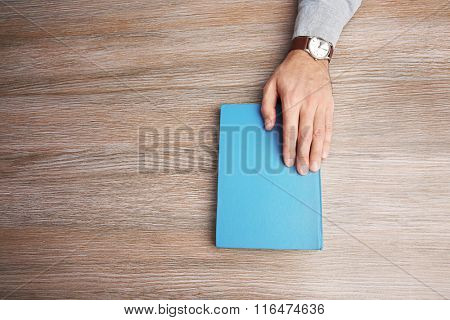 Man hand on book, on wooden table background