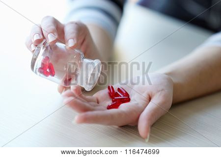 Woman spills red medical capsules  to her hand, close up