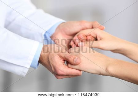 Hand of medical doctor carefully holding patient's hands