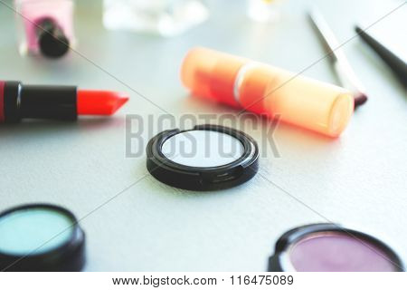 Red lipstick with eye shadows on a table