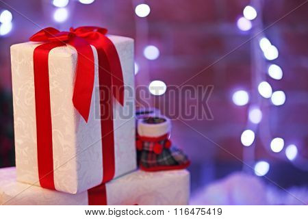 Christmas gift boxes and lights on blurred wall background