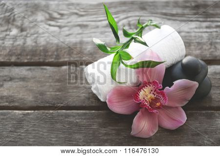 Spa stones with towel, pink orchid and bamboo on wooden background