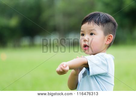 Young boy feeling itchy and scratching his arm