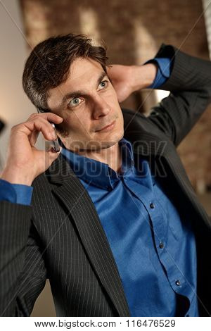 Thoughtful businessman talking on mobilephone, looking up, hand behind ear.