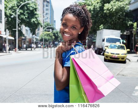 African American Woman With Shopping Bags In The City